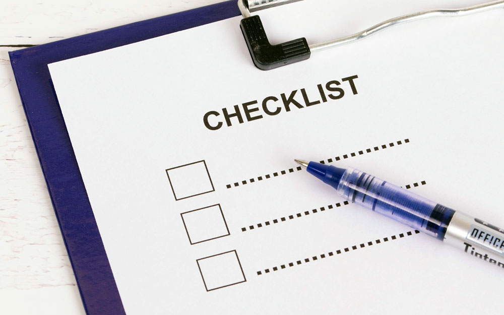 A blue pen on a paper with Checklist written on it