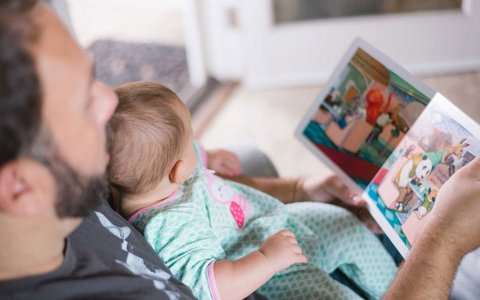 Man reading a book to a baby