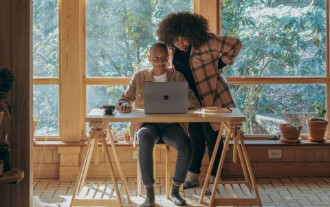 Man and woman looking over a laptop
