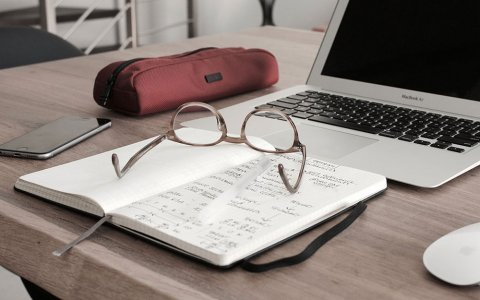 glasses sit on top of a notebook with a computer in the background