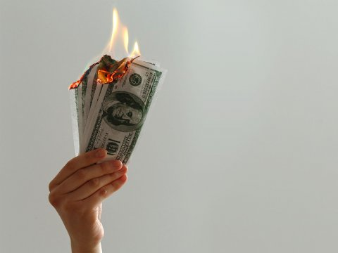 Hand holding money on fire