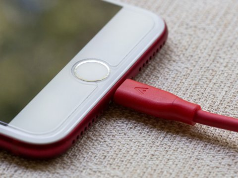 Cell phone connected to a red charger