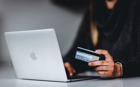 Woman holding a credit card next to a computer